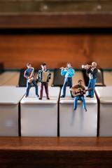 Kleine Musikerfiguren auf Klaviertasten