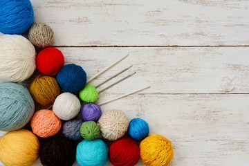 Balls of colorful yarn on white wooden background.