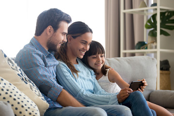 Beautiful family of mom dad and little kid child daughter sitting together on sofa smiling looking at smartphone screen taking selfie, making video call or recording vlog with cellphone at home