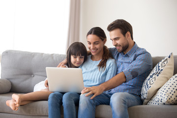 Happy family with kid daughter enjoy using laptop apps, making online call together, smiling parents and child girl relaxing having fun watching video on computer, doing internet shopping at home