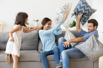Happy parents with kid daughter having fun pillow fight enjoying funny activity on weekend at home, cheerful family and little child girl playing laughing together throwing cushions in living room