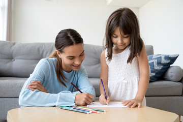 Cute child girl enjoys drawing with colored pencil on paper, mom or baby sitter helps kid teaching little daughter learning to draw at table play having fun with mother together at home or in daycare