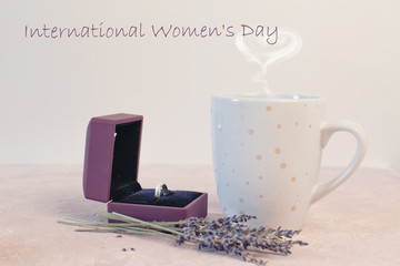 International Women's Day romantic dinner table setting marry me wedding engagement ring in box with lavender gift cup of coffee surprise on pink background with copyspace