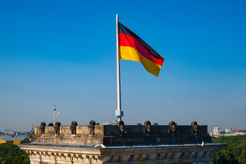 Berlin, Germany - Rooftop of the Reichstag building with the historic corner tower and Germany flag with Berlin skyline in background