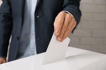 Man putting his vote into ballot box against brick wall, closeup