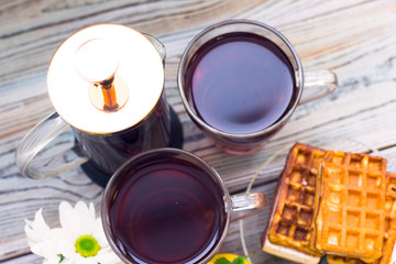 Black tea ceremony - waffles, glass full of tea, glass pot, sugar, yellow lemon, flower, tea leaves, spices on a wooden boards background