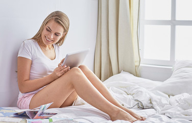 Happy young girl in bed using phone, tablet and maps to search