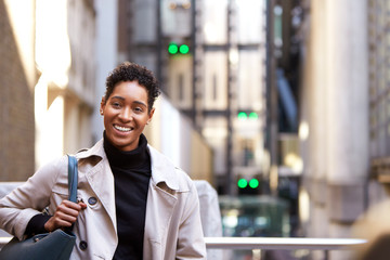 Close up of a millennial black businesswoman standing on a street in London smiling to camera, waist up