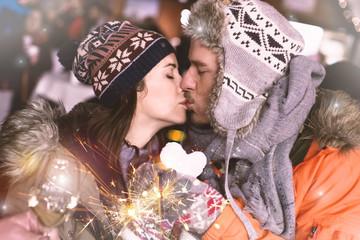 Verliebtes Paar hält Herz aus Schnee und küsst sich