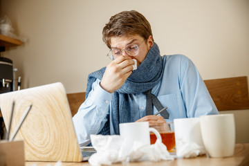 Sick man with handkerchief sneezing blowing nose while working in office, businessman caught cold, seasonal flu. Pandemic influenza, disease prevention, air conditioning in office cause sickness
