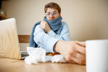 Feeling sick and tired. The man with cup of hot tea working in office, businessman caught cold, seasonal flu. Pandemic influenza, disease prevention, illness, virus, infection, temperature, fever and