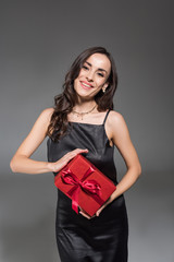 beautiful smiling woman holding red gift box isolated on grey