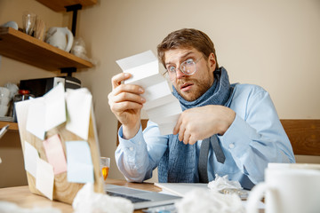 Sick man reading prescription medicine working in office, businessman caught cold, seasonal flu. Pandemic influenza, disease prevention, illness, virus, infection, temperature, fever and flu concept