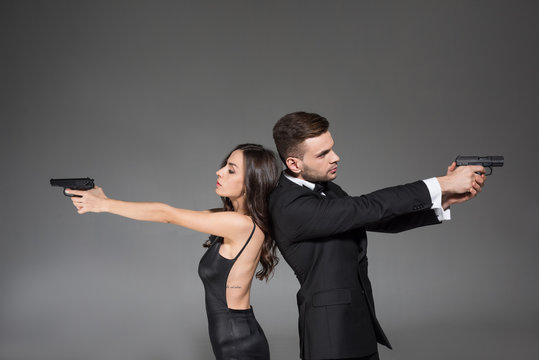 confident couple of secret agents in black clothes aiming with weapon, isolated on grey