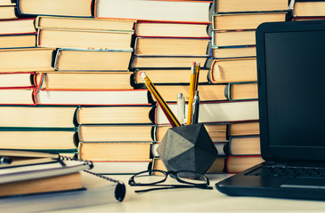 Stack of books, notebook, laptop, glasses in office background for education learning concept.