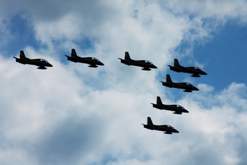 Terrible and frightening dark silhouettes of military jets in the blue sky. Symbol of war.