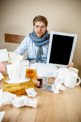 Sick man with empty poster for copyspace while working in office, businessman caught cold, seasonal flu. Pandemic influenza, disease prevention, illness, virus, infection, temperature, fever and flu