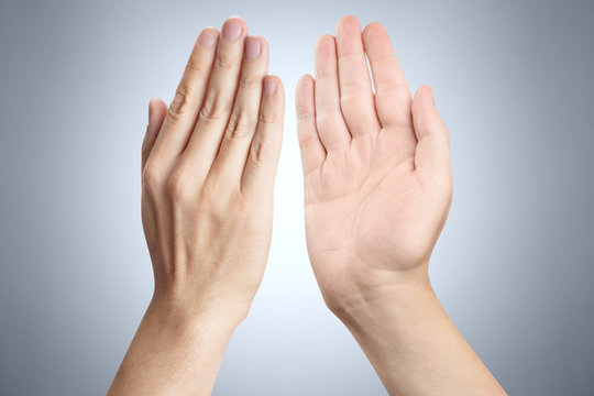Two hands giving high five to each other on gray background