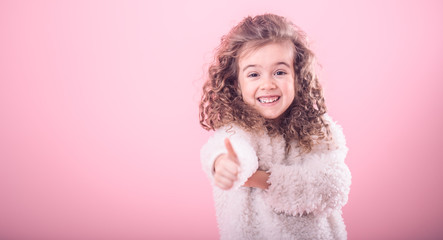 Portrait of girl pointing finger at up on pink