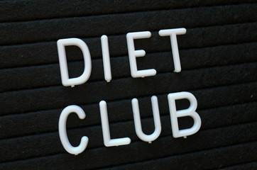 The words Diet Club in white plastic letters on a black letter board as a reminder of your Weight Loss resolution
