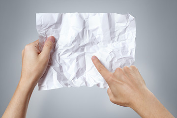 Hands holding and examining crumpled sheet of paper on gray background