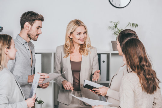 young businesspeople holding papers and looking at professional smiling mentor in office