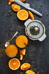 Summer drink. Fresh orange juice in tall glass with citrus squeezer and orange slices on dark concrete background. Top view, copy space for text. Selective focus.
