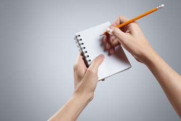 Hand writing in notepad using a pencil on gray background