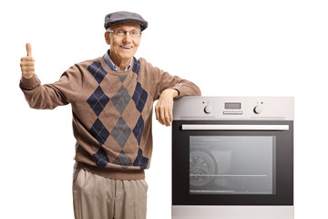 Elderly man standing with an electric oven and giving thumbs up