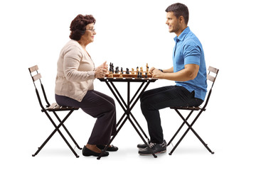 Senior woman playing chess with a young man
