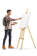 Teen student painting on a canvas