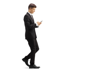 Young man in a black suit walking and typing onto a mobile phone