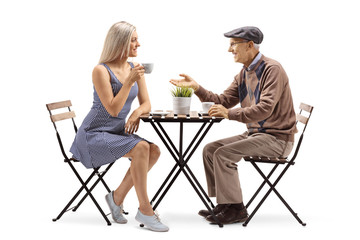 Elderly man sitting at a table and talking to a young woman drinking coffee