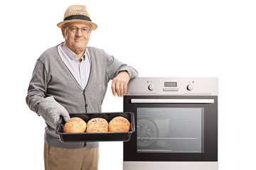 Mature man holding a tray with freshly baked bread loafs next to an oven