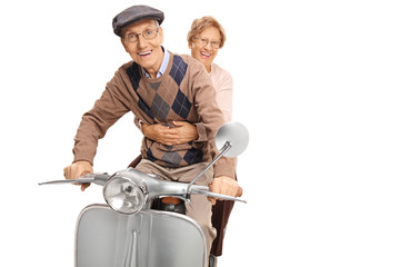 Senior happy couple riding a vintage motorbike