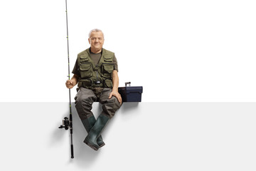 Mature fisherman with a fishing rod sitting on a panel