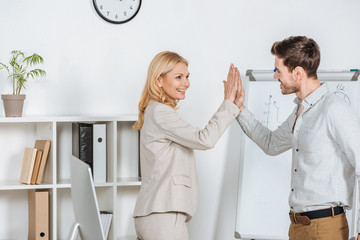 happy young businessman giving high five to mature mentor in office
