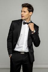 Handsome man in black suit preparing for wedding