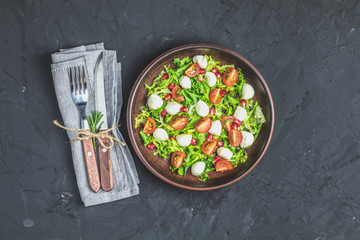 Salad with green lettuce mix served on a brown ceramic plate