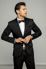 Young handsome man in black suit buttoning his jacket, isolated over gray background