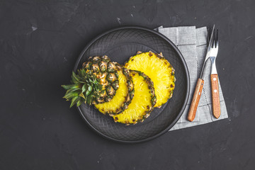Sliced pineapple in ceramic plate and set of cutlery