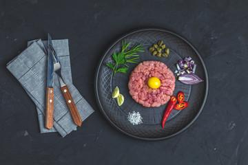 Steak tartare with yolk and ingredients on black ceramic plate