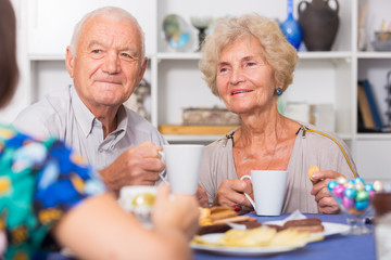 Smiling elderly spouses enjoying tea with girl