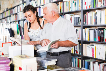 old man and a girl are looking for information in books