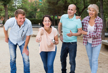 Smiling mature people playing petanque