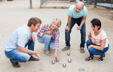 Cheerful males and females playing petanque