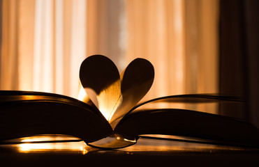 Valentine's day, heart from a book page against a beautiful sunset