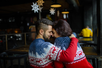 Young loving couple dressed in blue sweater sitting with knitted coffee cups in the cafe in winter