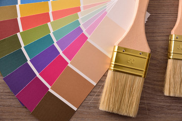 Colour chart in fan with two brushes on table top