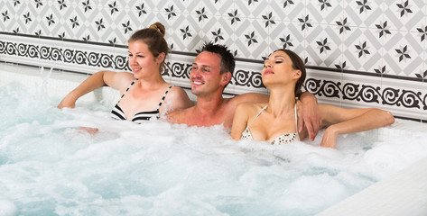 Two girls and guy are enjoying jacuzzi